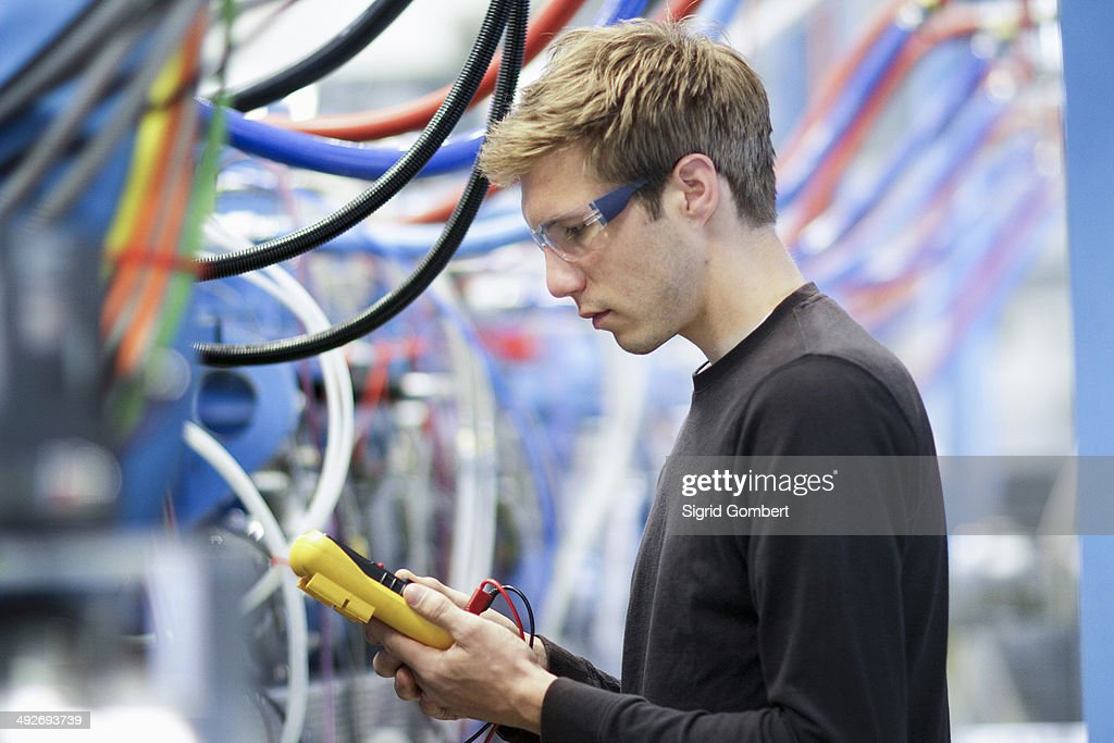 Mid adult male technician testing cables in engineering plant