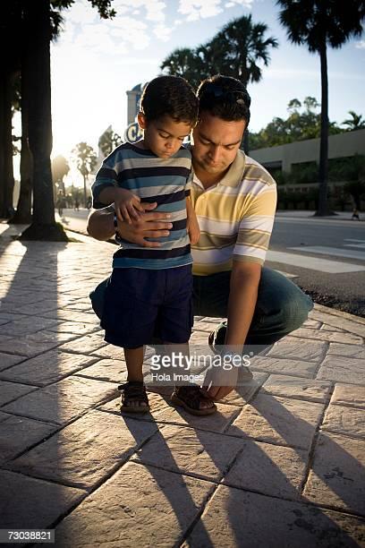 Mid adult man adjusting his son's sandals, Malecon, Santo Domingo, Dominican Republic