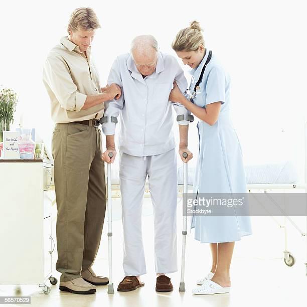 mid adult man and a female nurse helping a senior man walk with crutches