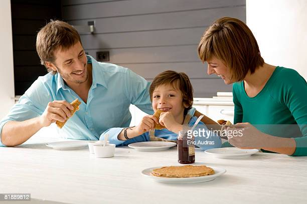 Mid adult man and a young woman having breakfast with their son