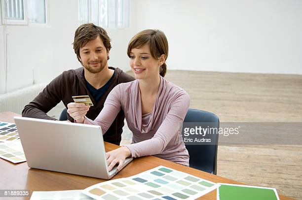 Mid adult man and a young woman using a laptop and holding a credit card