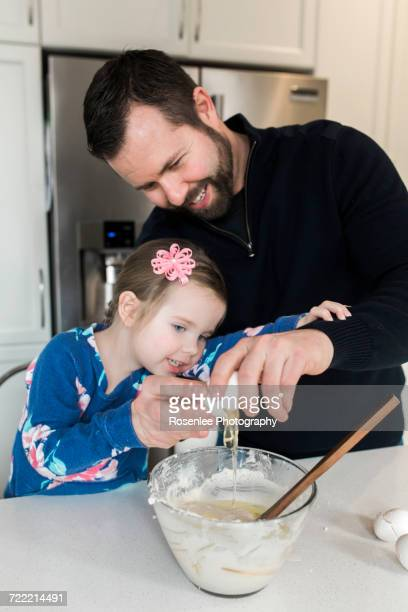 Mid adult man and daughter cracking egg into mixing bowl together at kitchen counter