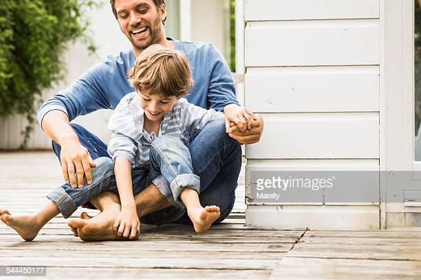 Mid adult man and son laughing and tickling feet on porch
