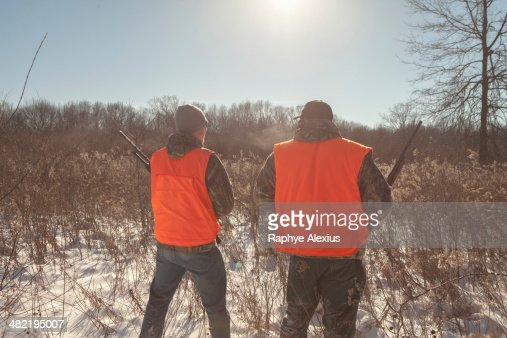 Mid adult man and teenage son hunting in Petersburg State Game Area, Michigan, USA