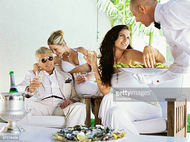 Mid adult man and two young women being served by a waiter