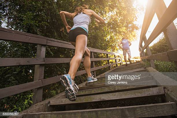 Mid adult man and young woman running up steps, rear, low angle view