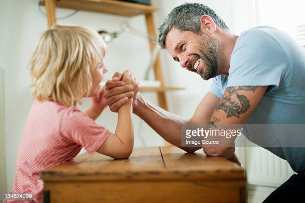 Mid adult man arm wrestling with son