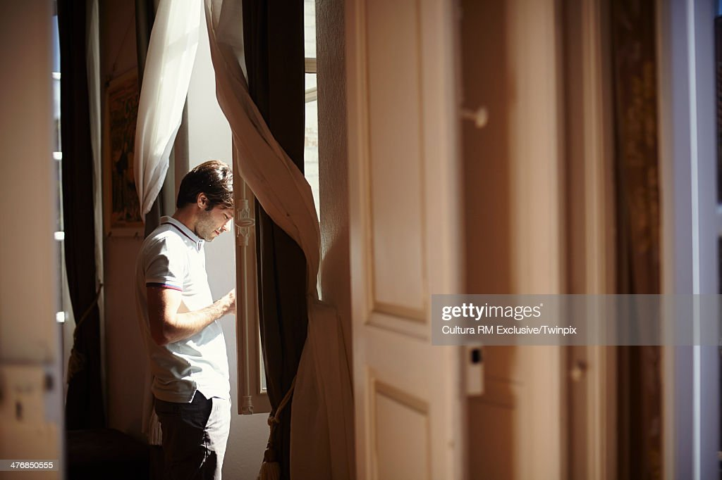 Mid adult man at apartment window using mobile phone : Stock Photo