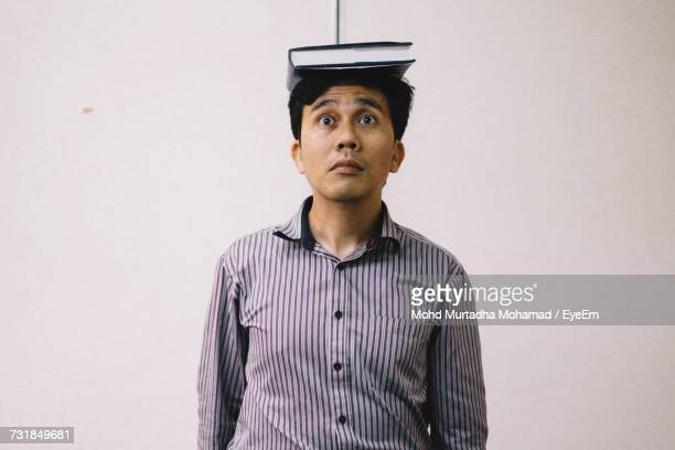 Mid Adult Man Balancing Book On Head While Standing Against Wall