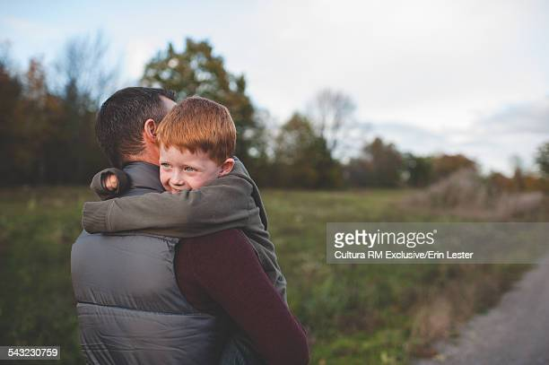 Mid adult man carrying and hugging son on rural road