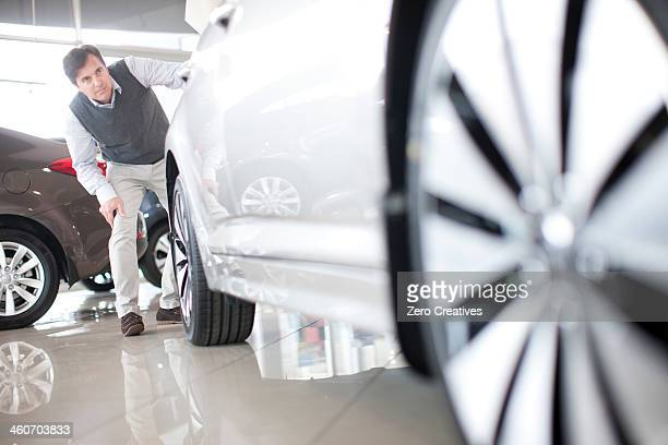 Mid adult man checking car in showroom
