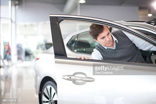 Mid adult man checking door in car showroom