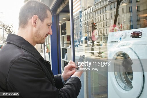 Mid adult man checking out washing machine in shop using smartphone : Stock Photo