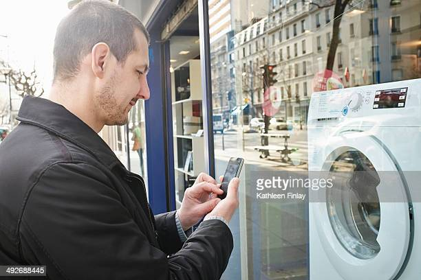 Mid adult man checking out washing machine in shop using smartphone