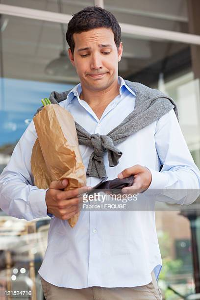 Mid adult man checking the empty wallet with paper bag full of vegetables