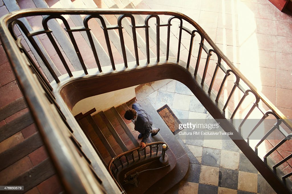 Mid adult man climbing lobby stairs : Stock Photo
