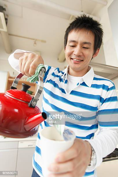 Mid adult man cooking instant noodle