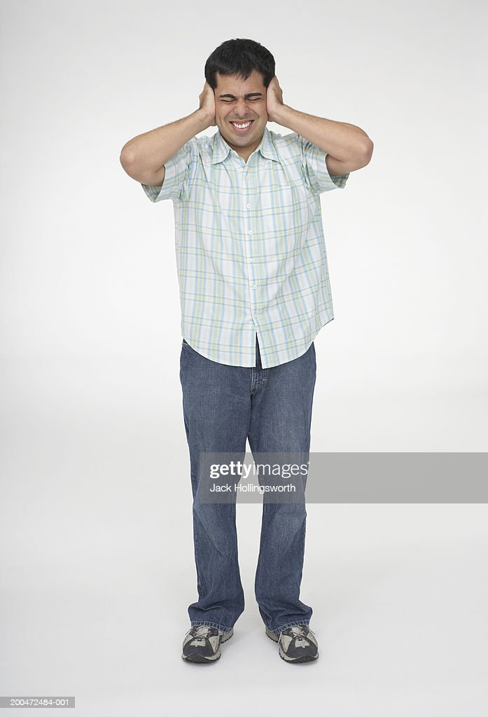 Mid adult man covering his ears with his hands