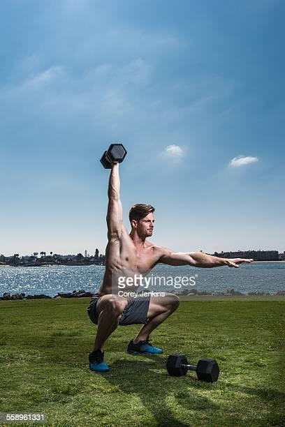 Mid adult man crouching and lifting dumb bells at coast