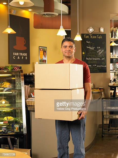 Mid adult man delivering boxes to cafe, portrait