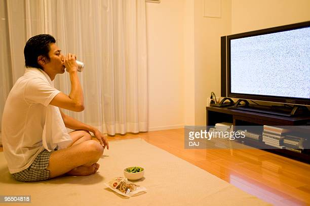 Mid adult man drinking beer while watching TV