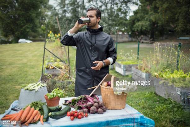 Mid adult man drinking coffee while standing by freshly harvested vegetables on table at urban garden