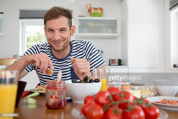 Mid adult man eating at kitchen table