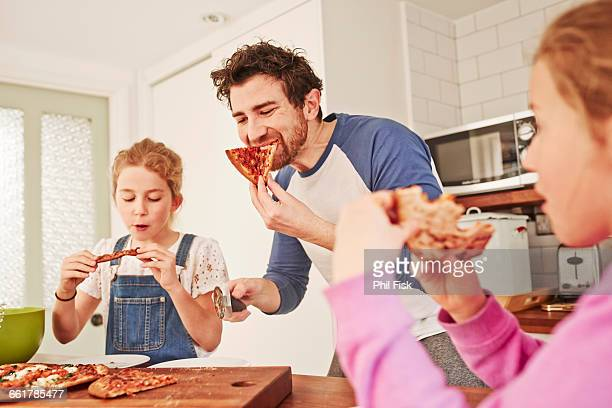 Mid adult man eating pizza with daughters at kitchen bench