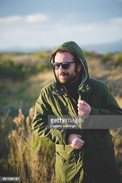 Mid adult man fastening anorak at coast, Sorso, Sassari, Sardinia, Italy