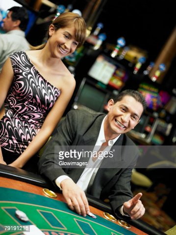 Mid adult man gambling in a casino and a young woman standing beside him : Foto de stock