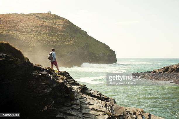 Mid adult man gazing out from rocky cliff, Boscastle, Cornwall, UK