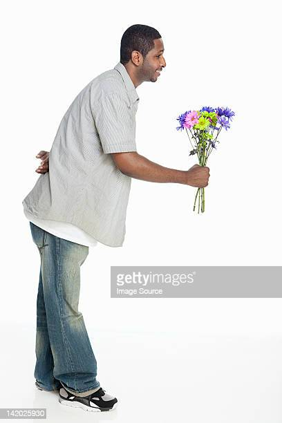 Mid adult man giving flowers against white background