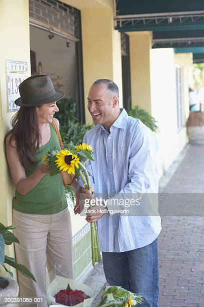 Mid adult man giving sunflowers to a mature woman