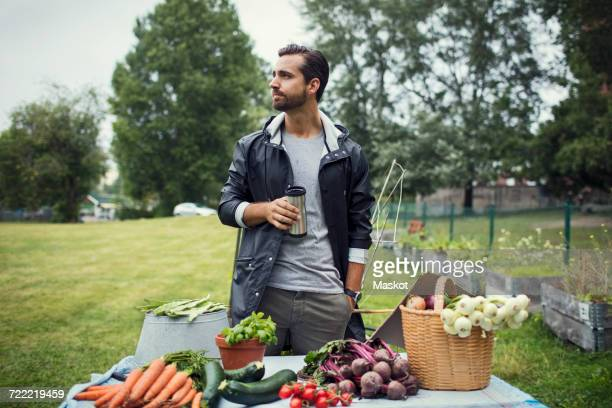 Mid adult man having coffee while standing by freshly harvested vegetables on table at urban garden