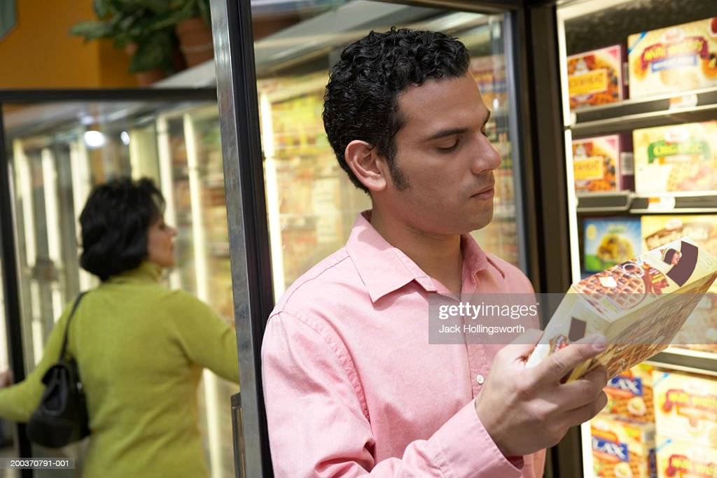 Mid adult man holding a box of frozen desert in a supermarket : Stock Photo