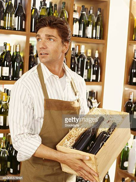 mid adult man holding a crate of wine bottles in a liquor store