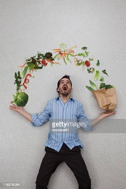 Mid adult man holding balancing vegetables with mouth open
