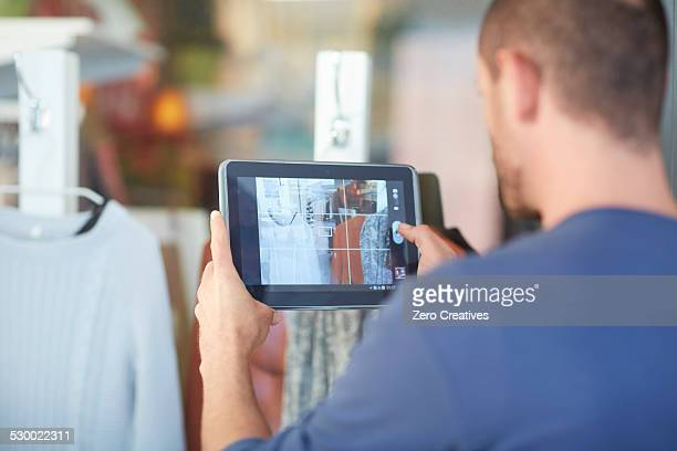 Mid adult man holding digital tablet, taking photograph of shop window