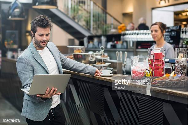 Mid adult man holding laptop while buying coffee at cafe