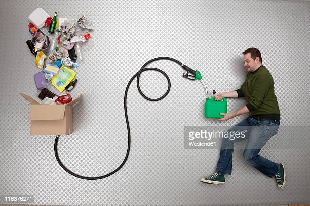 Mid adult man holding petrol can and hose connected to cardboard box