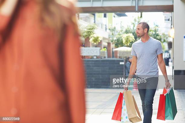 Mid adult man holding shopping bags, walking behind woman