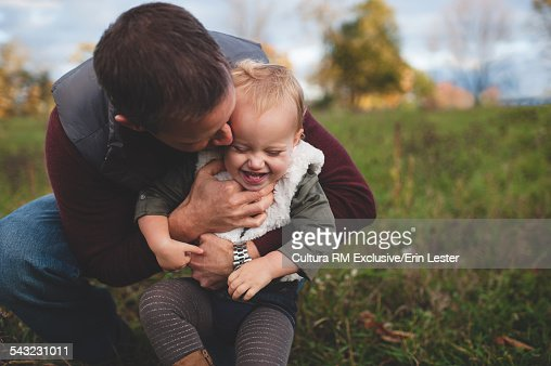 Mid adult man hugging and tickling toddler daughter in field