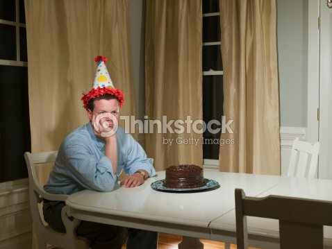 Mid Adult Man In Party Hat Sitting At Table Front Of Birthday Cake