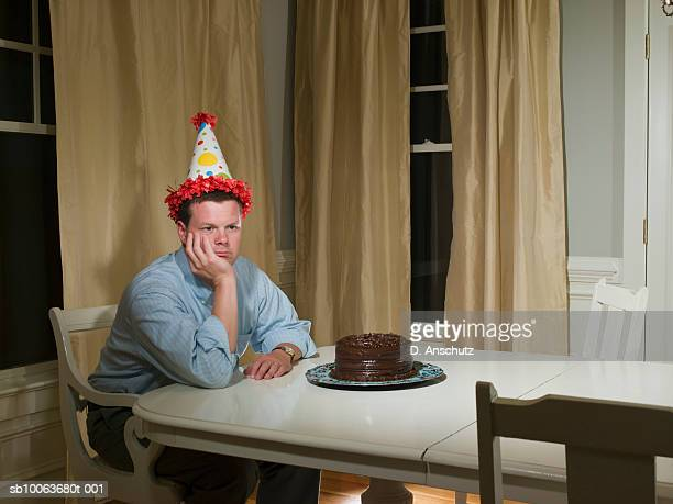 Mid adult man in party hat, sitting at table in front of birthday cake