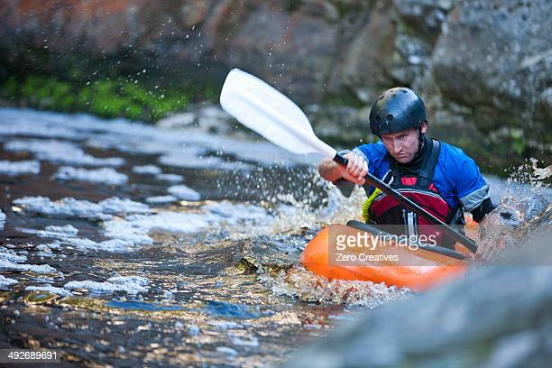 Mid adult man kayaking on river rapids