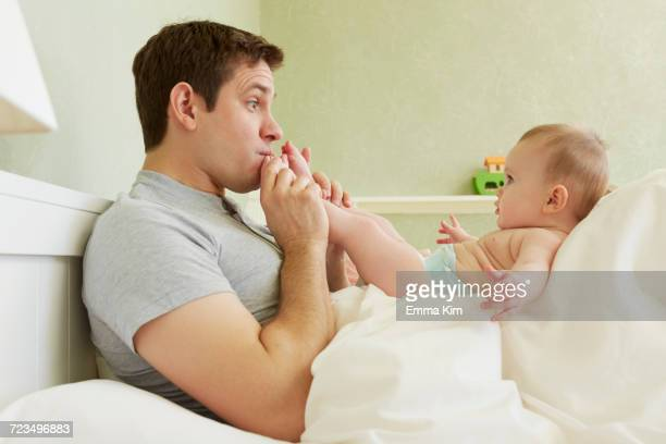 Mid adult man kissing baby daughters feet in bed
