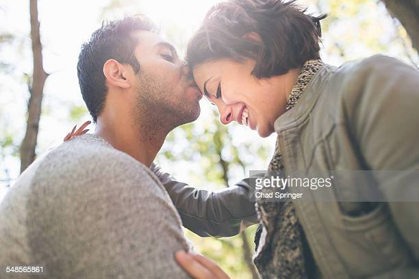Mid adult man kissing girlfriend on forehead in forest