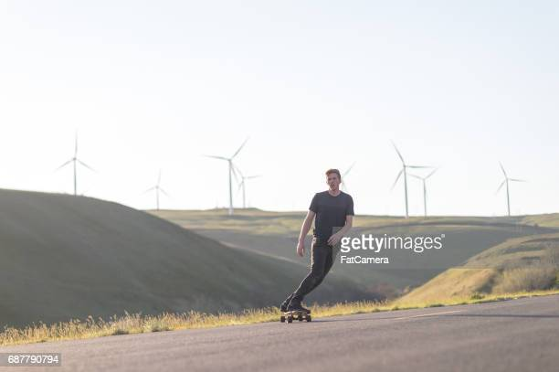Mid adult man longboards down rural highway surrounded by wind turbine farm