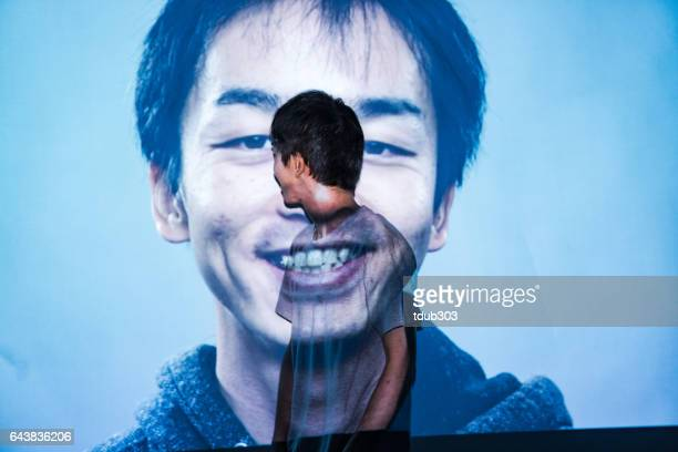 Mid adult man looking at a projected image of himeself