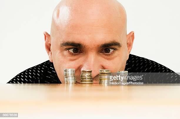 Mid adult man looking at a stack of coins on a table
